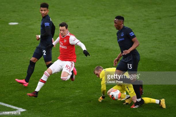 Mesut Ozil of Arsenal is challenged by Mason Holgate Yerry Mina and Jordan Pickford of Everton the Premier League match between Arsenal FC and...