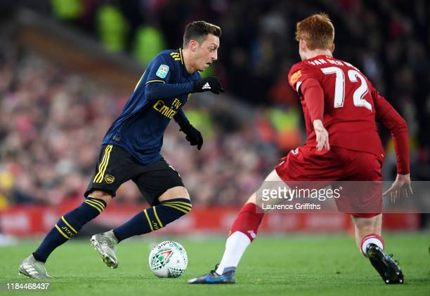 Mesut Ozil of Arsenal is challenged by Sepp Van Den Berg of Liverpool during the Carabao Cup Round of 16 match between Liverpool and Arsenal at...