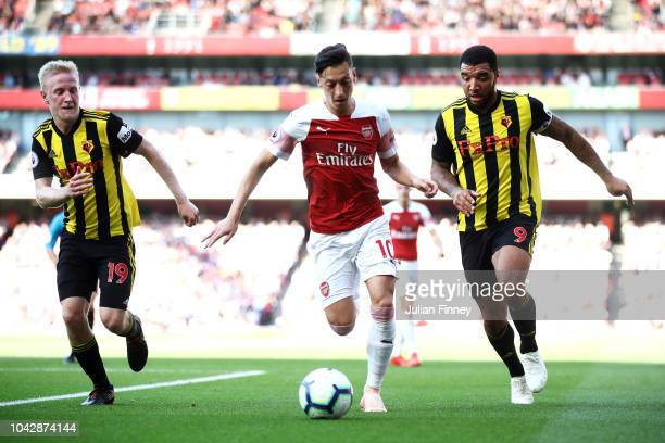 Mesut Ozil of Arsenal is challenged by Will Hughes of Watford and Troy Deeney of Watford during the Premier League match between Arsenal FC and...