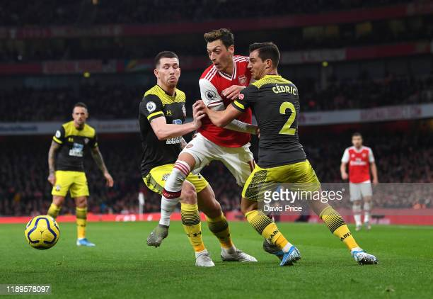 Mesut Ozil of Arsenal is chellenged by PierreEmile Hojbjerg and Cedric of Southampton during the Premier League match between Arsenal FC and...