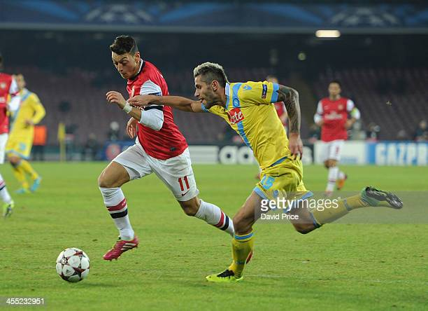 Mesut Ozil of Arsenal is closed down by Valon Behrami of Napoli during the match Napoli against Arsenal in the UEFA Champions League at Stadio San...