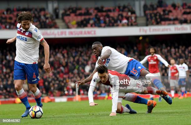 Mesut Ozil of Arsenal is fouled in the box by Bruno Martins Indi of Stoke City and a penalty is awarded during the Premier League match between...