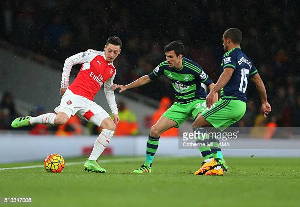 Mesut Ozil of Arsenal is marked by Jack Cork and Wayne Routledge of Swansea City during the Barclays Premier League match between Arsenal and Swansea...