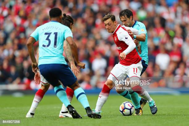 Mesut Ozil of Arsenal is put under pressure from Charlie Daniels of AFC Bournemouth during the Premier League match between Arsenal and AFC...