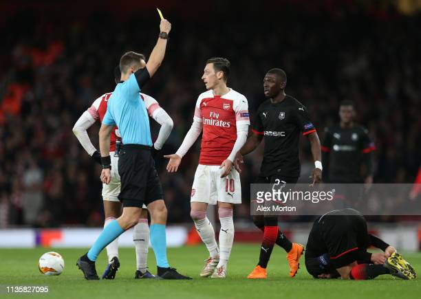 Mesut Ozil of Arsenal is shown a yellow card after a challenge on Benjamin Andre of Stade Rennais during the UEFA Europa League Round of 16 Second...