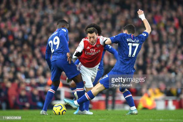 Mesut Ozil of Arsenal is tackled by Fikayo Tomori and Mateo Kovacic of Chelsea during the Premier League match between Arsenal FC and Chelsea FC at...