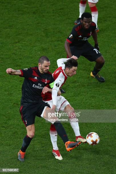 Mesut Ozil of Arsenal is tackled by Leonardo Bonucci of AC Milan during the UEFA Europa League Round of 16 second leg match between Arsenal and AC...
