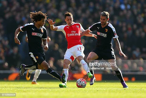Mesut Ozil of Arsenal is tackled by Nathan Ake and Valon Behrami of Watford during the Emirates FA Cup match between Arsenal and Watford at the...