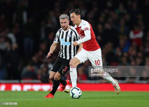 Mesut Ozil of Arsenal is watched by Paul Dummett of Newcastle United during the Premier League match between Arsenal FC and Newcastle United at...