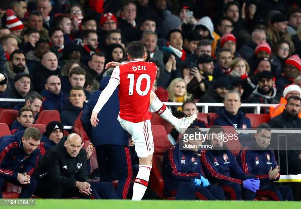 Mesut Ozil of Arsenal kicks a water bottle as he is subbed as Interim Manager of Arsenal Freddie Ljungberg looks on during the Premier League match...