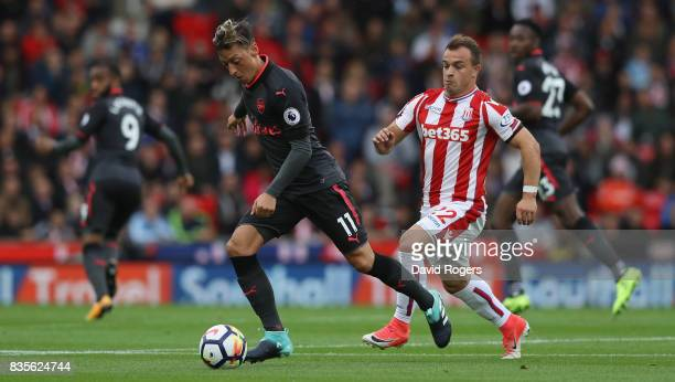 Mesut Ozil of Arsenal moves away from Xherdan Shaqiri during the Premier League match between Stoke City and Arsenal at Bet365 Stadium on August 19...