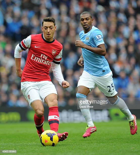Mesut Ozil of Arsenal passes under pressure from Fernandinho of Man City during match between Manchester City verses Arsenal Barclays Premier League...