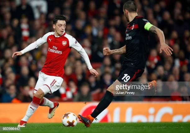 Mesut Ozil of Arsenal runs at Leonardo Bonucci of AC Milan during the UEFA Europa League Round of 16 match between Arsenal and AC Milan at Emirates...