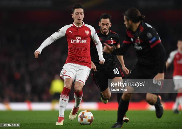 Mesut Ozil of Arsenal runs at Ricardo Rodriguez and Hakan Calhanoglu of MIlan during the match between Arsenal and AC Milan at Emirates Stadium on...