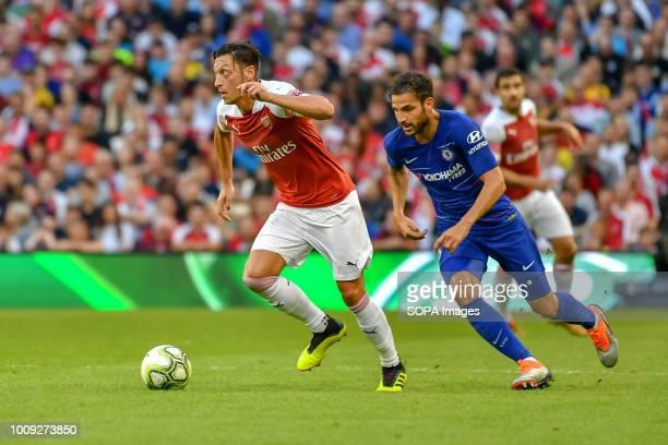 Mesut Ozil of Arsenal runs from Cesc Fabergas of Chelsea during the Chelsea v Arsenal International Champions Cup in Aviva Stadium