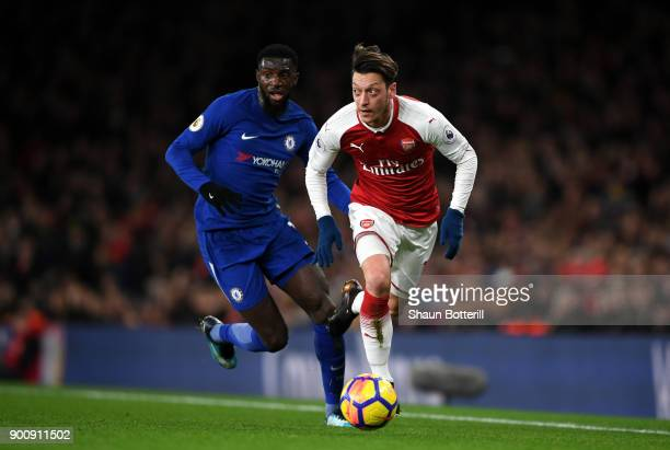 Mesut Ozil of Arsenal runs with the ball as Tiemoue Bakayoko of Chelsea chases him down during the Premier League match between Arsenal and Chelsea...