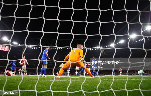 Mesut Ozil of Arsenal scores his sides first goal past Kasper Schmeichel of Leicester City during the Premier League match between Arsenal FC and...