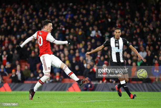 Mesut Ozil of Arsenal scores his sides third goal during the Premier League match between Arsenal FC and Newcastle United at Emirates Stadium on...