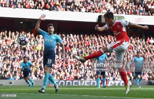 Mesut Ozil of Arsenal scores his sides third goal during the Premier League match between Arsenal and Swansea City at Emirates Stadium on October 15...