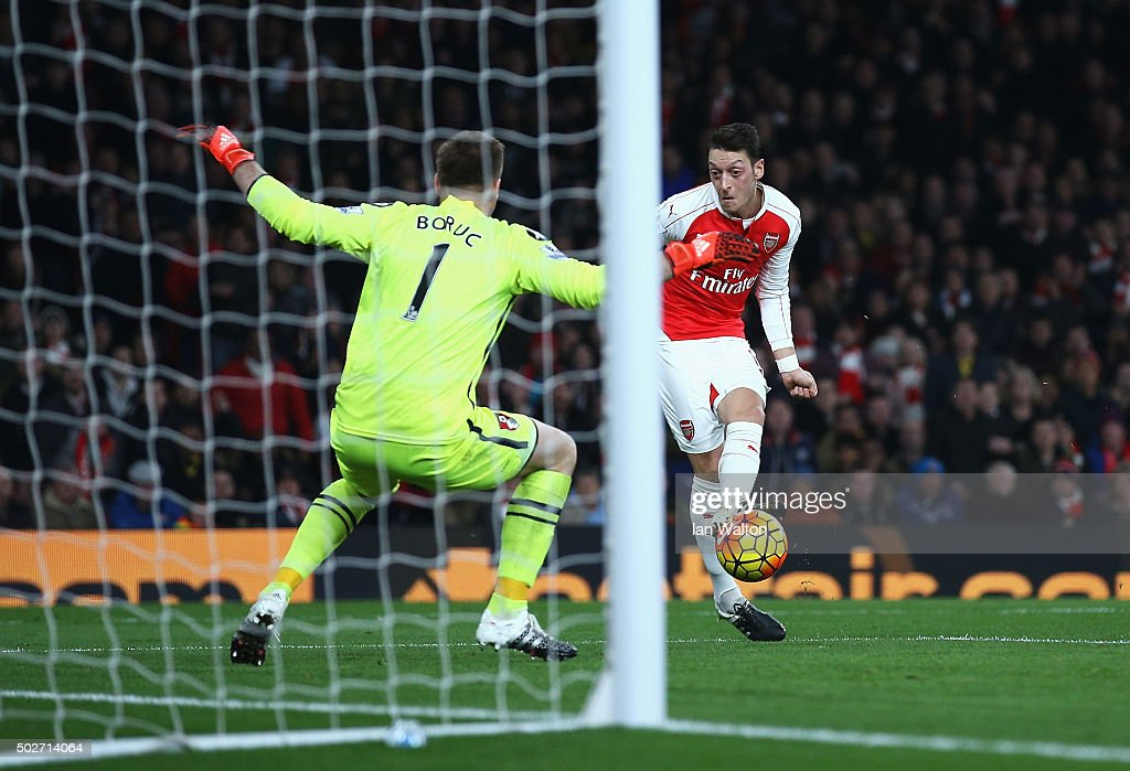 Mesut Ozil of Arsenal scores his team's second goal past Artur Boruc of Bournemouth during the Barclays Premier League match between Arsenal and A.F.C. Bournemouth at Emirates Stadium on December 28, 2015 in London, England.