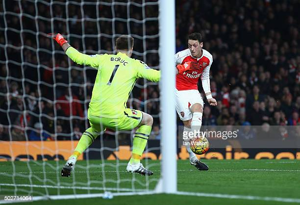 Mesut Ozil of Arsenal scores his team's second goal past Artur Boruc of Bournemouth during the Barclays Premier League match between Arsenal and AFC...