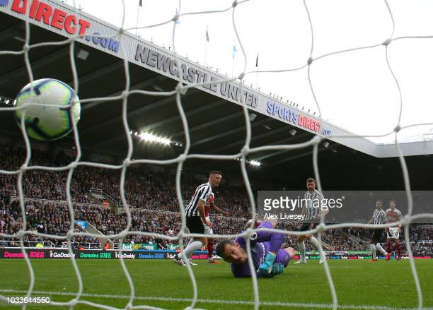 Mesut Ozil of Arsenal scores his team's second goal past Martin Dubravka of Newcastle United during the Premier League match between Newcastle United...