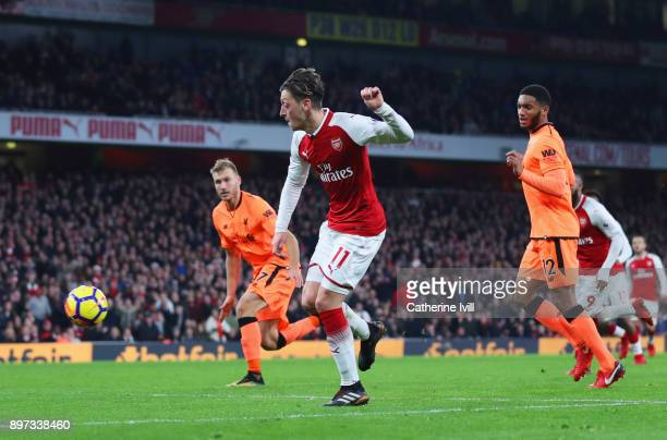 Mesut Ozil of Arsenal scores their third goal during the Premier League match between Arsenal and Liverpool at Emirates Stadium on December 22 2017...