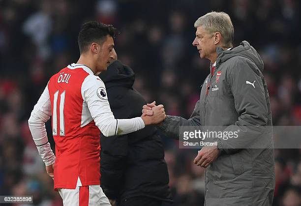 Mesut Ozil of Arsenal shakes hands with Arsene Wenger Manager of Arsenal after substituted during the Premier League match between Arsenal and...