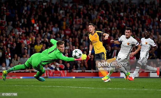 Mesut Ozil of Arsenal shoots at goal past Tomas Vaclik of Basel during the UEFA Champions League group A match between Arsenal FC and FC Basel 1893...