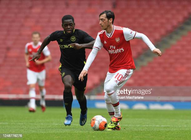 Mesut Ozil of Arsenal takes on Dru Yearwood of Brentford during a friendly match between Arsenal and Brentford at Emirates Stadium on June 10 2020 in...