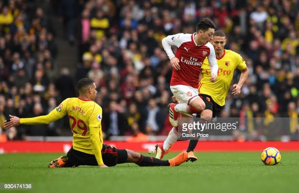 Mesut Ozil of Arsenal takes on Etienne Capoue of Watford during the Premier League match between Arsenal and Watford at Emirates Stadium on March 11...