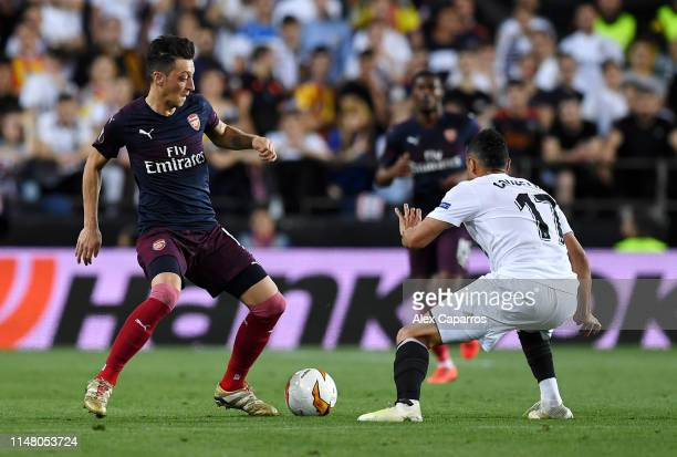 Mesut Ozil of Arsenal takes on Francis Coquelin of Valencia during the UEFA Europa League Semi Final Second Leg match between Valencia and Arsenal at...