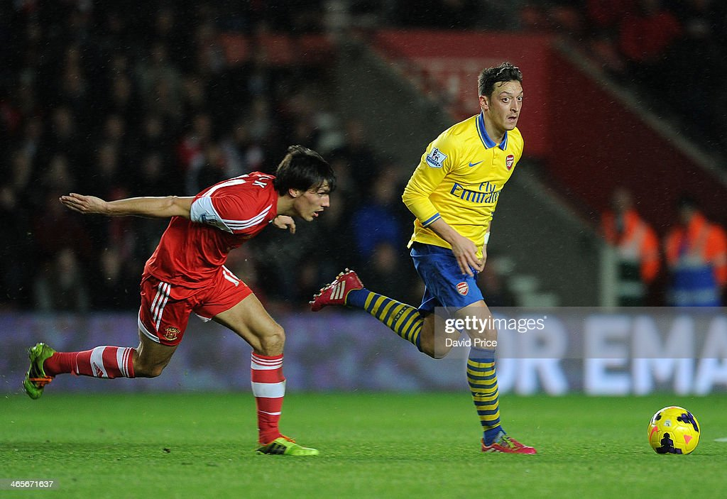 Mesut Ozil of Arsenal takes on Jack Cork of Southampton during the match between Southampton and Arsenal at St Mary's Stadium on January 28, 2014 in Southampton, England.