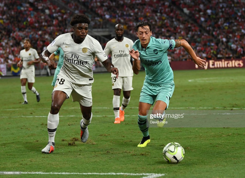 Mesut Ozil of Arsenal takes on Loic Mbe Soh of PSG during the International Champions Cup match between Arsenal and Paris Saint Germain at the National Stadium on July 28, 2018 in Singapore.