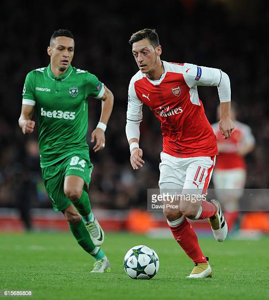 Mesut Ozil of Arsenal takes on Marcelinho of Ludogorets during the UEFA Champions League match between Arsenal FC and PFC Ludogorets Razgrad at...