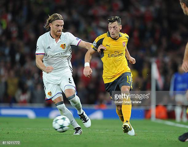 Mesut Ozil of Arsenal takes on Michael Lang of Basel during the UEFA Champions League match between Arsenal FC and FC Basel 1893 at Emirates Stadium...