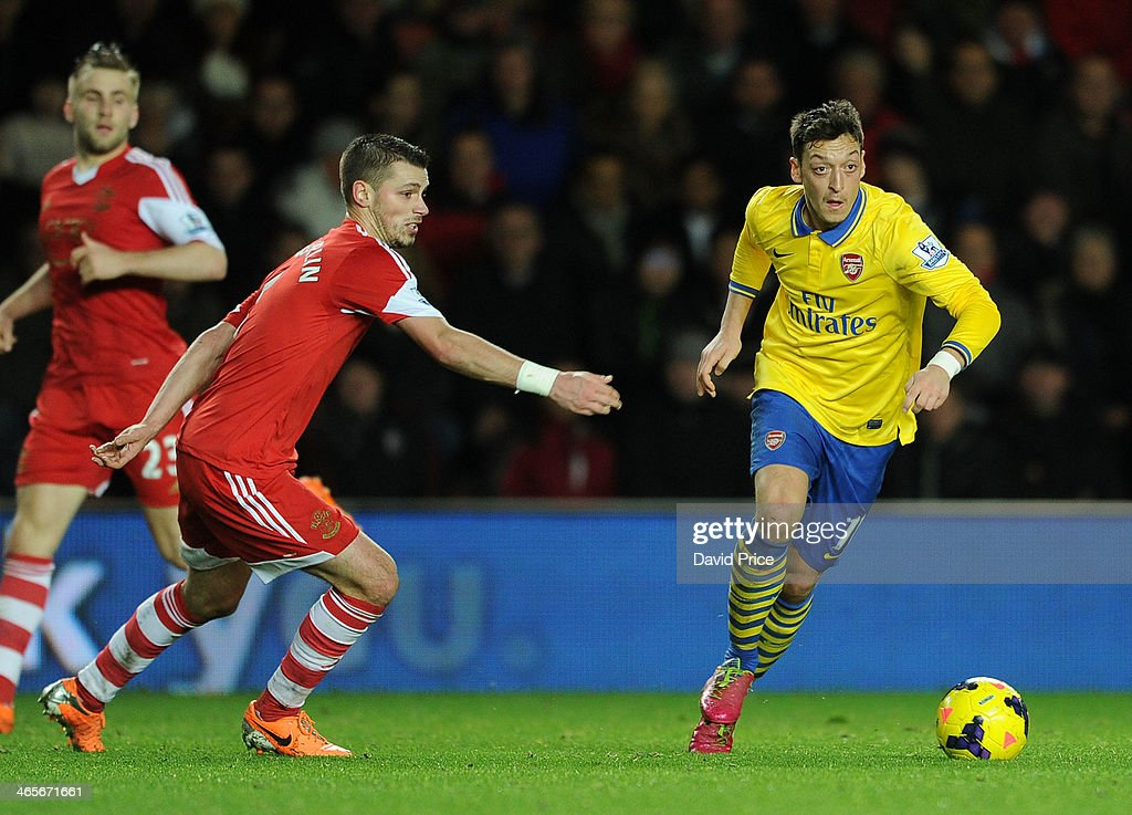 Mesut Ozil of Arsenal takes on Morgan Schneiderlin of Southampton during the match between Southampton and Arsenal at St Mary's Stadium on January 28, 2014 in Southampton, England.