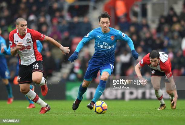Mesut Ozil of Arsenal takes on Oriol Romeu and PierreEmile Hojbjerg of Southampton during the Premier League match between Southampton and Arsenal at...