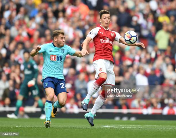 Mesut Ozil of Arsenal takes on Ryan Fraser of Bournemouth during the Premier League match between Arsenal and AFC Bournemouth at Emirates Stadium on...