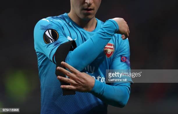 Mesut Ozil of Arsenal ties up the black armband during the UEFA Europa League Round of 16 match between AC Milan and Arsenal at the San Siro on March...