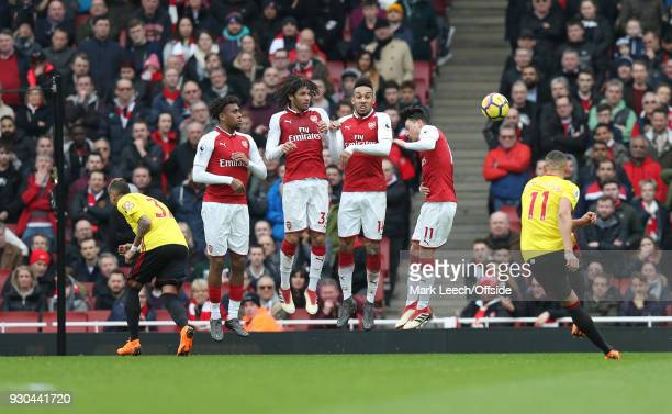 Mesut Ozil of Arsenal turns his back in the defensive wall as Richarlison of Watford takes a free kick during the Premier League match between...