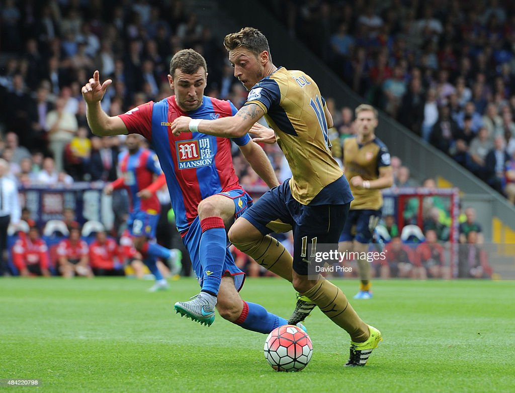 Mesut Ozil of Arsenal under pressure from James McArthur of Crystal Palace during the Barclays Premier League match between Crystal Palace and Arsenal on August 16, 2015 in London, United Kingdom.