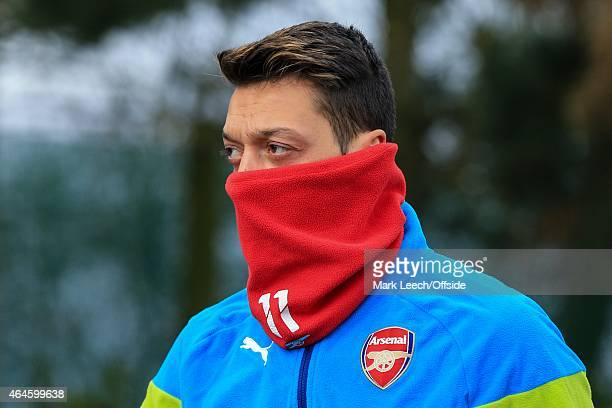 Mesut Ozil of Arsenal wearing a snood pulled up over his face during the Arsenal training session ahead of the UEFA Champions League round of 16...