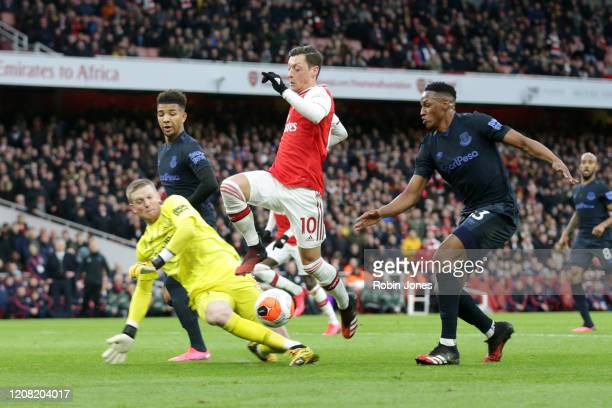 Mesut Ozil of Arsenal with Jordan Pickford and ev of Everton during the Premier League match between Arsenal FC and Everton FC at Emirates Stadium on...
