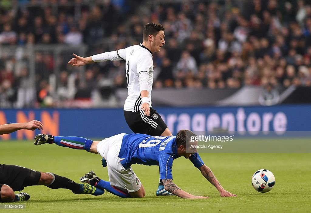Mesut Ozil (L) of Germany and Federico Bernardeschi (R) of Italy vie for the ball during the friendly football match between Germany and Italy in the Allianz Arena in Munich, Germany on March 29, 2016.