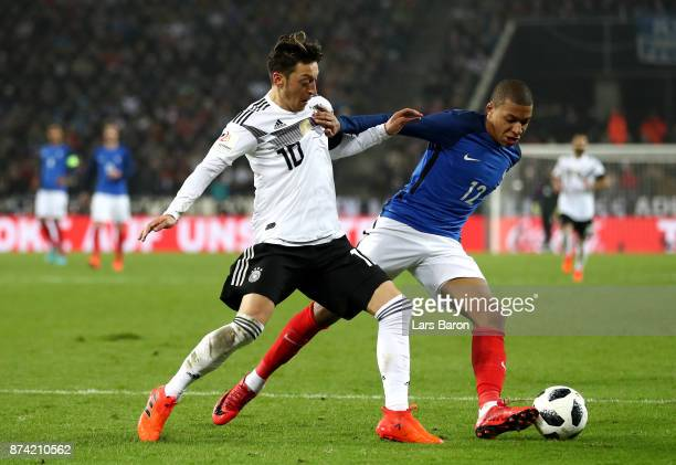 Mesut Ozil of Germany and Kylian Mbappe of France battle for possession during the international friendly match between Germany and France at...