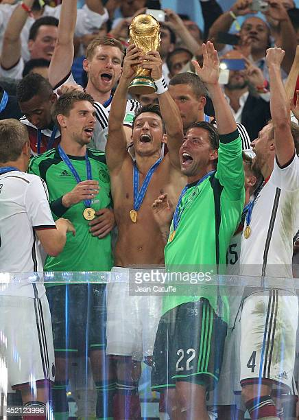 Mesut Ozil of Germany holds the trophy and celebrate the victory with his teammates during the trophy presentation after the 2014 FIFA World Cup...