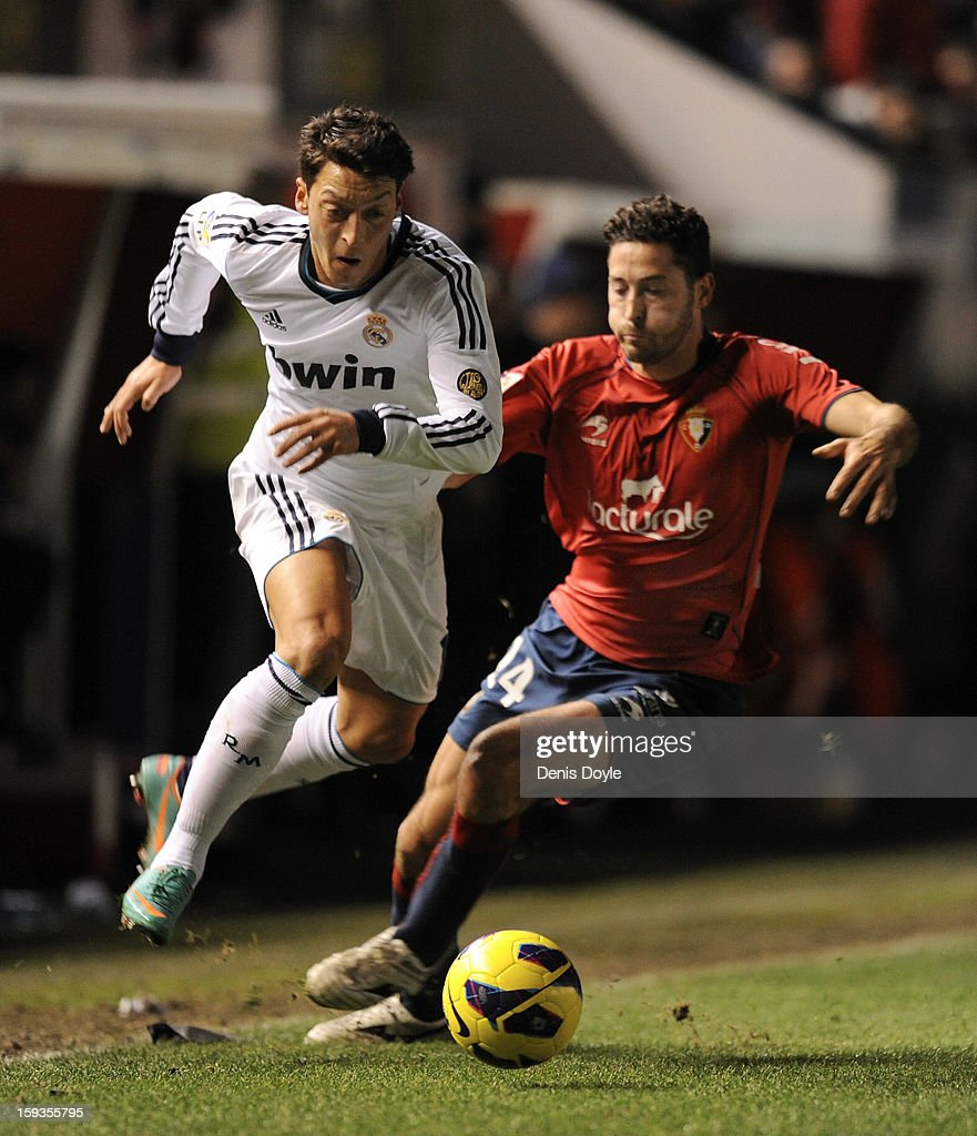 Mesut Ozil (L) of Real Madrid battles for the ball against Alejandro Arribas of Osasuna during the La Liga match between Osasuna and Real Madrid at estadio Reino de Navarra on January 12, 2013 in Pamplona, Spain.
