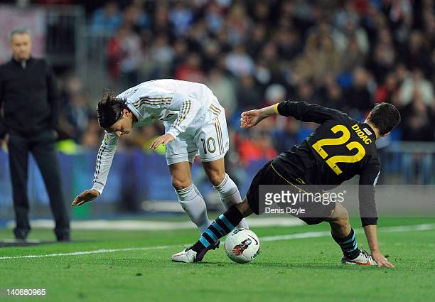 Mesut Ozil of Real Madrid battles for the ball against Didac Vila of RCD Espanyol during the La Liga match between Real Madrid and RCD Espanyol at...