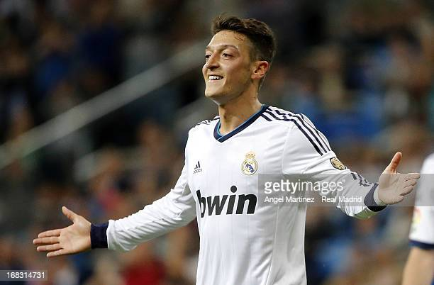 Mesut Ozil of Real Madrid celebrates after scoring his side's third goal during the La Liga match between Real Madrid and Malaga at Estadio Santiago...
